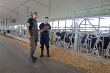Male dairy farmer talking with female ABS genetic advisor