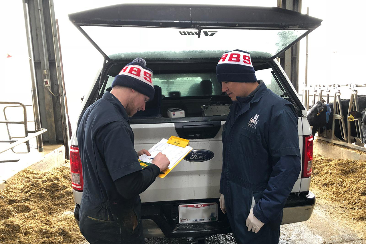 Two A.I. technicians discuss data report behind a truck.